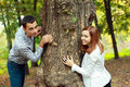 Young couple being playful around the tree Royalty Free Stock Photography