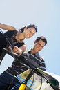 Young couple on bicycles reading map low angle view of against clear sky Stock Photos