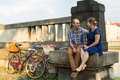 Young couple with bicycles sitting on the parapet love Royalty Free Stock Photos