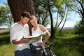 Young couple on a bike ride checking map Royalty Free Stock Photo