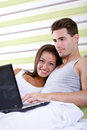 Young couple browsing the internet in bed Royalty Free Stock Image