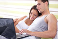 Young couple browsing the internet from their own bed Royalty Free Stock Photos