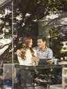 Young couple in cafe sitting next to windows with tablet computer Stock Image