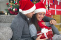 A young couple celebrate christmas night boy surprising girl with gift in Royalty Free Stock Photos