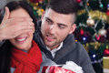 A young couple celebrate christmas night boy surprising girl with gift in Royalty Free Stock Images