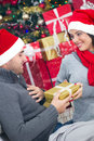 A young couple celebrate christmas night girl surprising boy with gift in Stock Photography