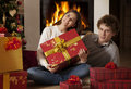 Young couple celebrating christmas holidays happy in front of a fireplace and looking at camera they are Stock Photo