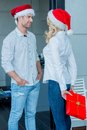 Young couple celebrating christmas in their festive red santa hats with the wife hiding a present for her husband behind her back Royalty Free Stock Images