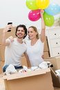 Young couple celebrating their new home laughing as they take a self portrait on smartphone for family and friends Royalty Free Stock Photo
