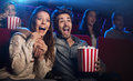 Young couple at the cinema watching an horror movie Royalty Free Stock Photo