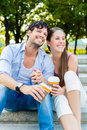 Young couple in city park drinking coffee man and women or and sitting summer on stairs Stock Image