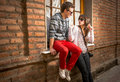 Young couple in the city sitting on a brick wall Stock Images