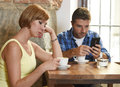 Young couple at coffee shop with internet and mobile phone addict man ignoring frustrated woman Royalty Free Stock Photo