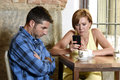 Young couple at coffee shop with internet and mobile phone addict woman ignoring frustrated man Royalty Free Stock Photo