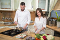 Young couple cooking and preparing food in the kitchen. Royalty Free Stock Photo