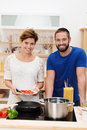 Young couple cooking spaghetti together in the kitchen standing at the stove with their pots and ingredients smiling at the camera Stock Photos