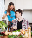 Young couple cooking together in kitchen Stock Images