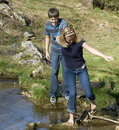 Young couple crossing a creek Stock Photos