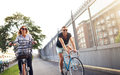 Young couple cycling in an urban park as they enjoy a healthy outdoor lifestyle the fresh air and summer sun Royalty Free Stock Photo