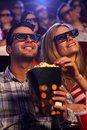 Young couple in d movie sitting auditorium of multiplex theater watching eating popcorn smiling Stock Images