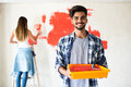 Young couple decorate their new apartment.They painting new home Royalty Free Stock Photo