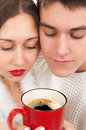 Young couple drinking hot coffee isolated in white Royalty Free Stock Image