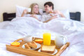 Young couple eating breakfast in bed . Royalty Free Stock Photo