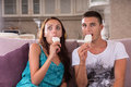 Young couple eating ice cream bars and watching tv enjoying while enthralled in television program or film at home while sitting Royalty Free Stock Photo