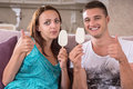 Young couple eating ice cream and giving thumbs up bars sign to camera while sitting on sofa at home Royalty Free Stock Photo