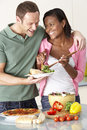 Young Couple Eating Meal In Kitchen Stock Images