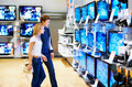 Young couple in electronics store looking at TVs Stock Images