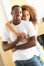 Young Couple Embracing In Living Room Stock Photography