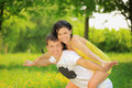 Young couple enjoying backriding outdoors Royalty Free Stock Photo