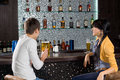 Young couple enjoying a beer at the bar date drinking sitting counter chatting with display of alcohol bottles on Stock Photography