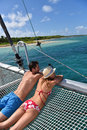 Young couple enjoying the catamaran s view on the sea suntanning a net Royalty Free Stock Images