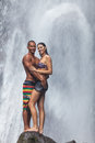 Young couple enjoying the freshness of nature under a waterfall in the tropics Royalty Free Stock Photo