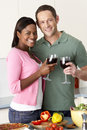 Young Couple Enjoying Glass Of Wine In Kitchen Stock Photo