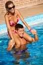 Young couple enjoying summer holiday smiling attractive in swimming pool having fun Stock Photo
