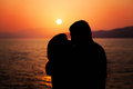 Young Couple Enjoying the Sunset on the Beach. Kiss