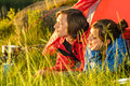 Young couple enjoying sunset from tent lying in camping Royalty Free Stock Photography