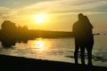 Young couple enjoying the sunset two silhouettes Stock Photography