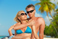 Young couple enjoying their vacation beautiful at maldives portrait with sunglasses and palm trees at background close up Royalty Free Stock Image