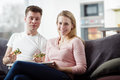 Young couple enjoying themselves and eating pizza on the sofa in the living room men women relaxing having fun Royalty Free Stock Photography