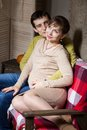 Young couple expecting a baby sitting on the couch while enjoying the moment Stock Photography