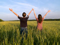 Young Couple in Field Holding Hands Up Royalty Free Stock Photo