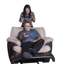 Young couple fighting over a tv remote control happy men taking and changing channels while his angry wife is ready to choke him Royalty Free Stock Image