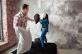 Young couple fighting pillows in the loft style bedroom Royalty Free Stock Photo