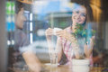 Young couple on first date drinking coffee shot through window Stock Photography