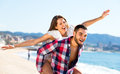 Young couple fooling around on beach and laughing the Royalty Free Stock Photos