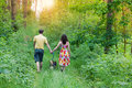 Young couple in the forest holding hands and walking with their dog Royalty Free Stock Photos